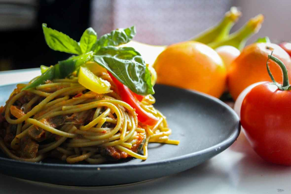 pasta with vegetable dish on gray plate beside tomato fruit on white table